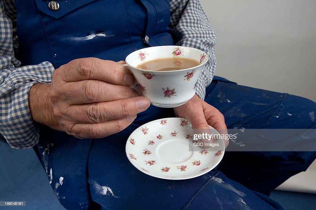 A labourer holds a delicate cup of tea and saucer : Stock Photo