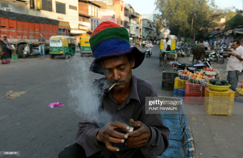 A labourer lights a bidi (leaf cigarette) as he sits on his cycle carrier in the old city of Ahmedabad on November 16, 2012. Widening income gaps and rising numbers of unskilled young people could derail India's economic growth, speakers at a high-profile economic conference warned on November 8. AFP PHOTO/ PUNIT PARANJPE