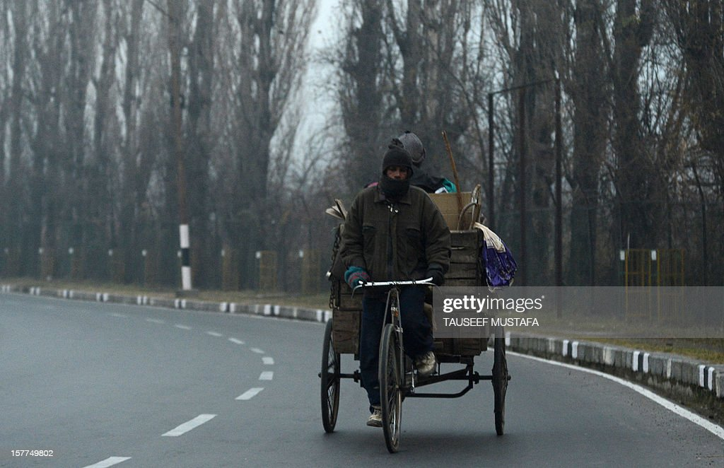 A labourer rides his tricycle with his wares during a cold spell in Srinagar on December 6, 2012. A cold wave further tightened its grip in Jammu and Kashmir with most places in the state recording sub-zero temperatures. AFP PHOTO/Tauseef MUSTAFA