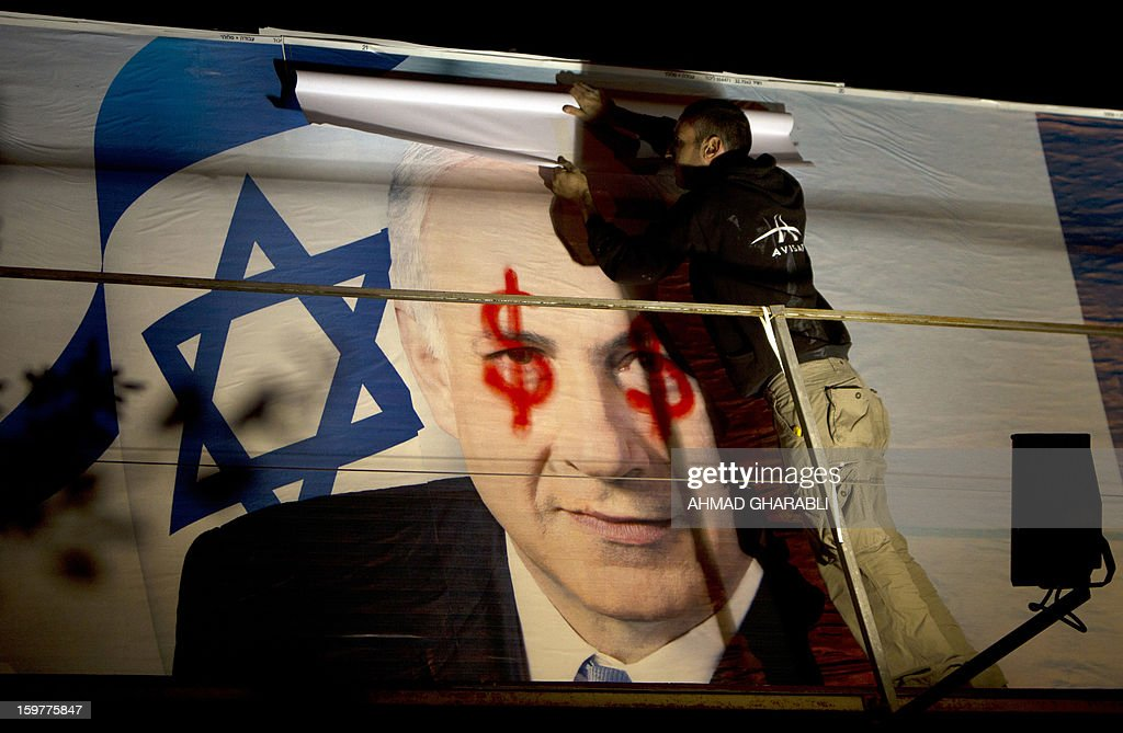 A labourer unrolls a new campaign poster over an identical one of Israel's Prime Minister Benjamin Netanyahu that was defaced with spray-painted red dollar signs over his eyes, two days before a general election, on a Jerusalem billboard on January 20, 2013.