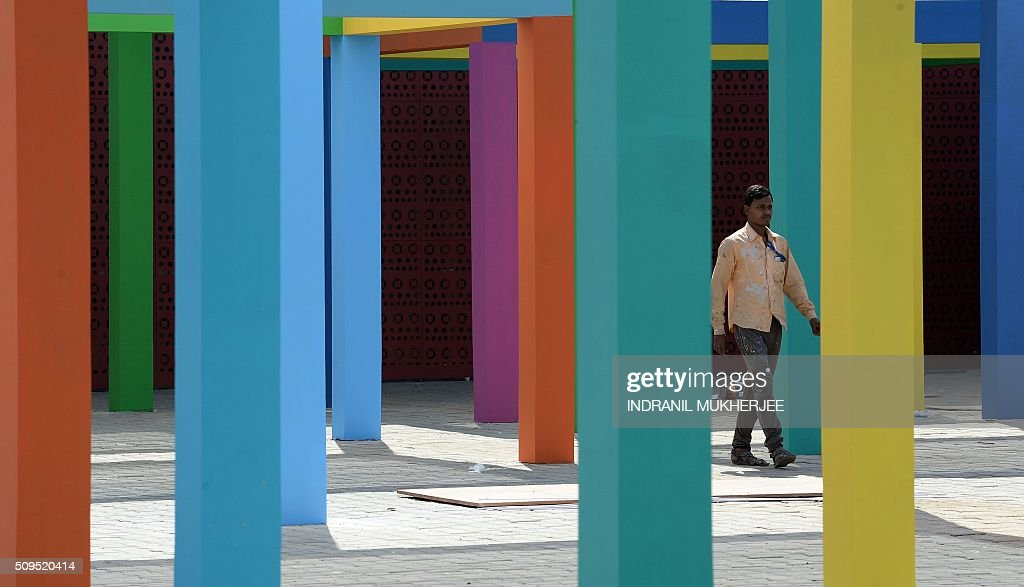 A labourer walks past an installation at the venue for the 'Make in India' showcase week in Mumbai on February 11, 2016. Over 190 companies, including national conglomerates and multinational corporations, 5,000 delegates from 60 countries, and leading industrialists including Ratan Tata and Mukesh Ambani will be participating in the maiden 'Make in India' showcase to be held in Mumbai from February 13-18. AFP PHOTO/ INDRANIL MUKHERJEE / AFP / INDRANIL MUKHERJEE