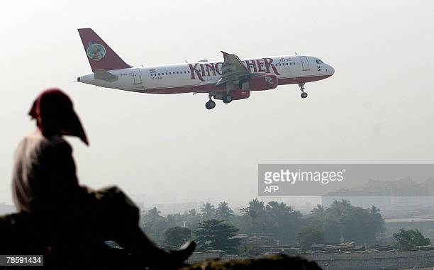 A labourer watches a Kingfisher Airline flight take off from the city airport in Mumbai 20 December 2007 India's biggest discount carrier Deccan will...