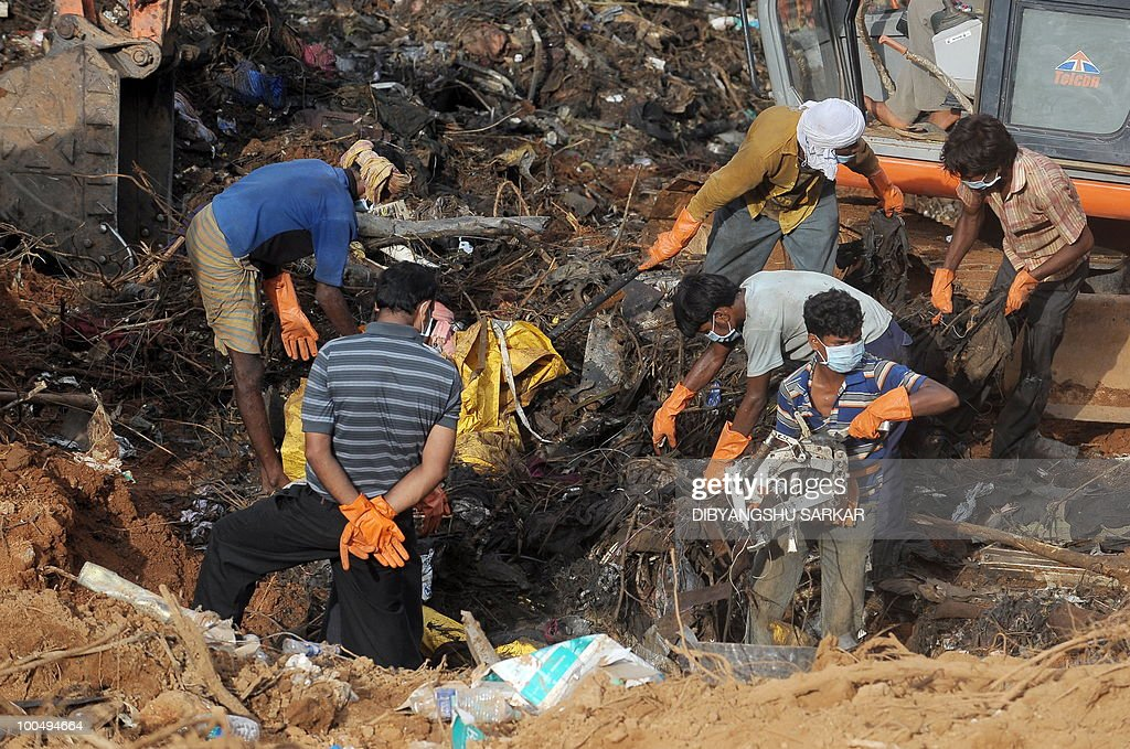 Labourers assist Director General of Civil Aviation (DGCA) officials in finding the 'black box' at the crash site of the doomed Air India Express flight 812 in Mangalore on May 25, 2010. Investigators recovered May 25 the 'black box' digital flight recorder that holds crucial clues to the crash of an Air India Express plane in southern India that killed 158 people. The discovery followed an intense three-day search that began hours after the Boeing 737-800, flying from Dubai to the city of Mangalore, overshot the runway May 22, plunged into a gorge and burst into flames.AFP PHOTO/Dibyangshu Sarkar