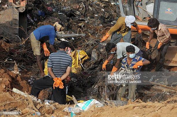 Labourers assist Director General of Civil Aviation officials in finding the 'black box' at the crash site of the doomed Air India Express flight 812...