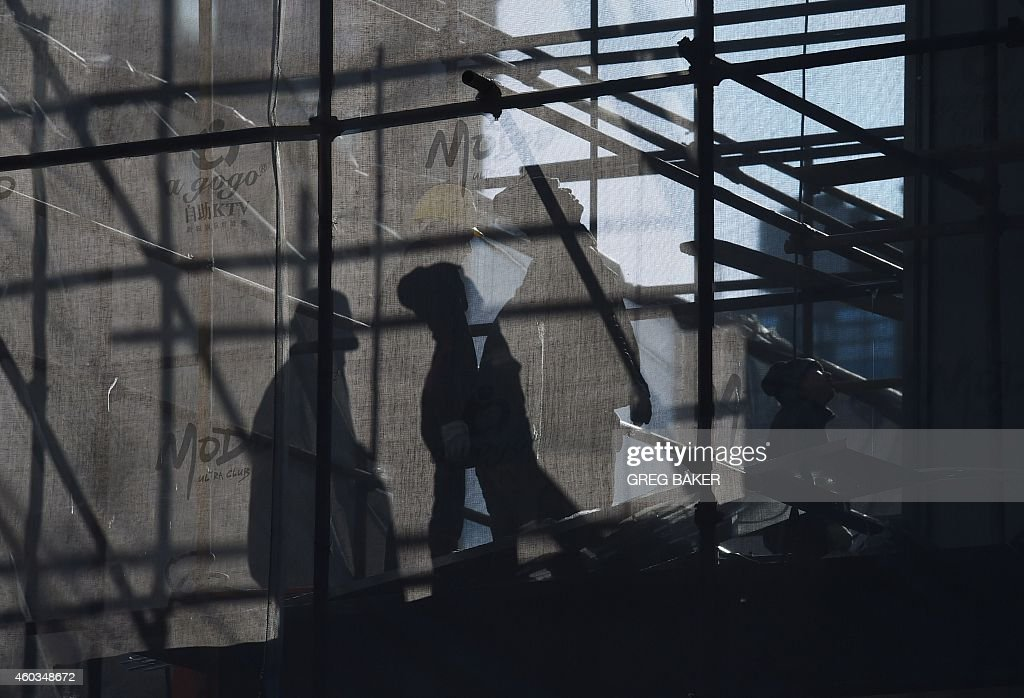 Labourers cast shadows while working on scaffolding outside a shopping mall in Beijing on December 12, 2014. Retail sales, a key indicator of consumer spending, increased 11.7 percent in China in November, official data showed on December 12, while fixed asset investment, a measure of government spending on infrastructure, expanded 15.8 percent on-year in the first 11 months -- the lowest since growth of 13.7 percent for the full year of 2001. AFP PHOTO/Greg BAKER