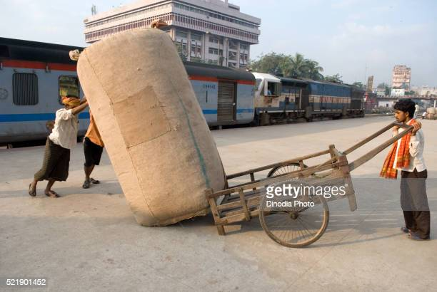 Labourers dragging luggage at railway platform, Guwhati, Assam, India