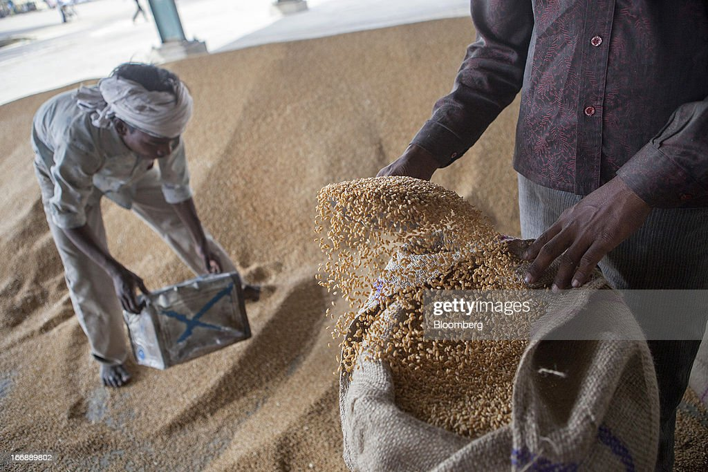 Labourers pack harvested wheat in gunny sacks for sale at a grain market in the district of Jalandhar in Punjab, India, on Tuesday, April 16, 2013. Wheat harvest in India, the second-biggest grower, may reach a record for a sixth straight year after farmers increased use of high-yielding seeds and winter rains boosted crop prospects, a state-run researcher said. Photographer: Prashanth Vishwanathan/Bloomberg via Getty Images
