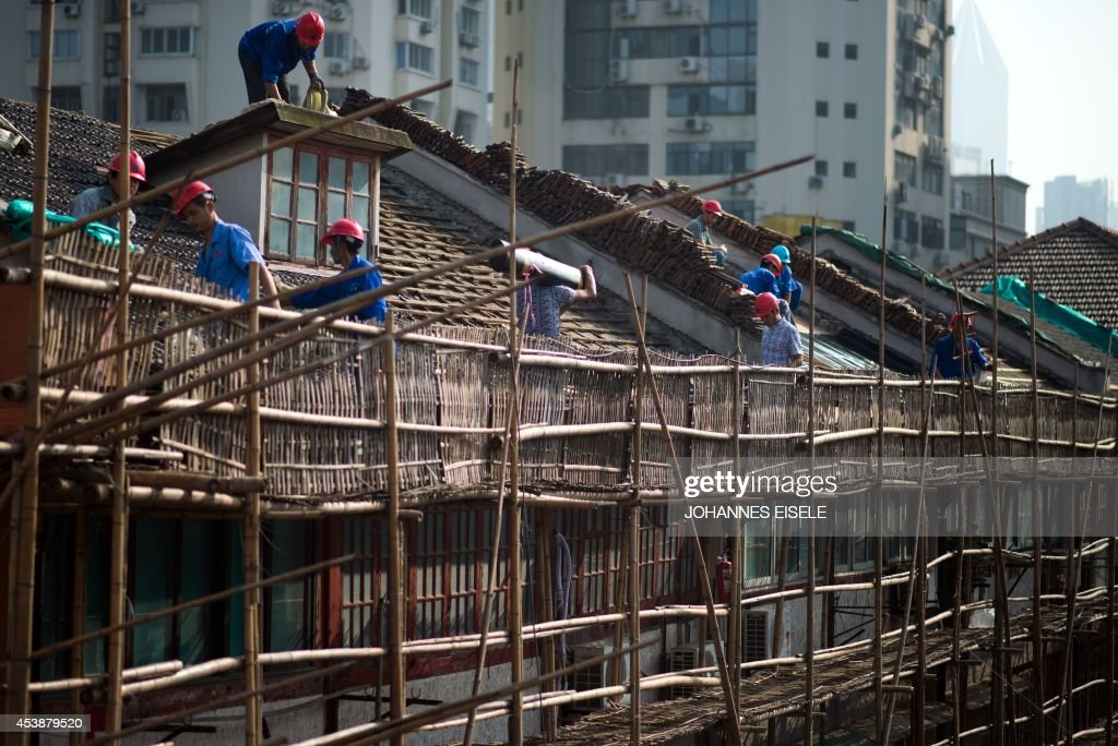 Labourers renovate a roof of a residential lane house in Shanghai on August 21, 2014. Foreign direct investment (FDI) into China dropped by more than a sixth year-on-year to a two-year low in July, the government said, but denied any link to Beijing's multiple probes into foreign companies.