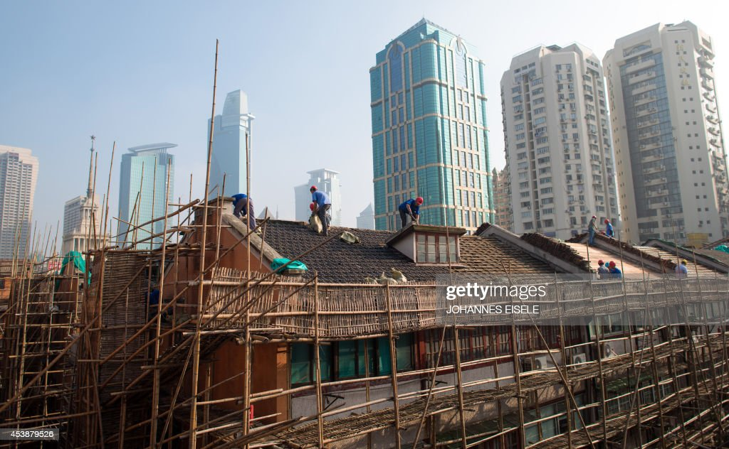 Labourers renovate a roof of a residential lane house in Shanghai on August 21, 2014. Foreign direct investment (FDI) into China dropped by more than a sixth year-on-year to a two-year low in July, the government said, but denied any link to Beijing's multiple probes into foreign companies. AFP PHOTO / JOHANNES EISELE
