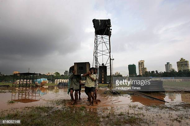 Labourers shifting the sound systems from Shivaji Park ground after the organisers had to postpone the election rally of Congress president Sonia...