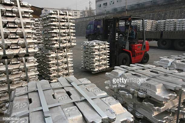 Labourers transport aluminium ingots at a storage of aluminium plant in Yuncheng Shanxi province January 7 2010 VCP
