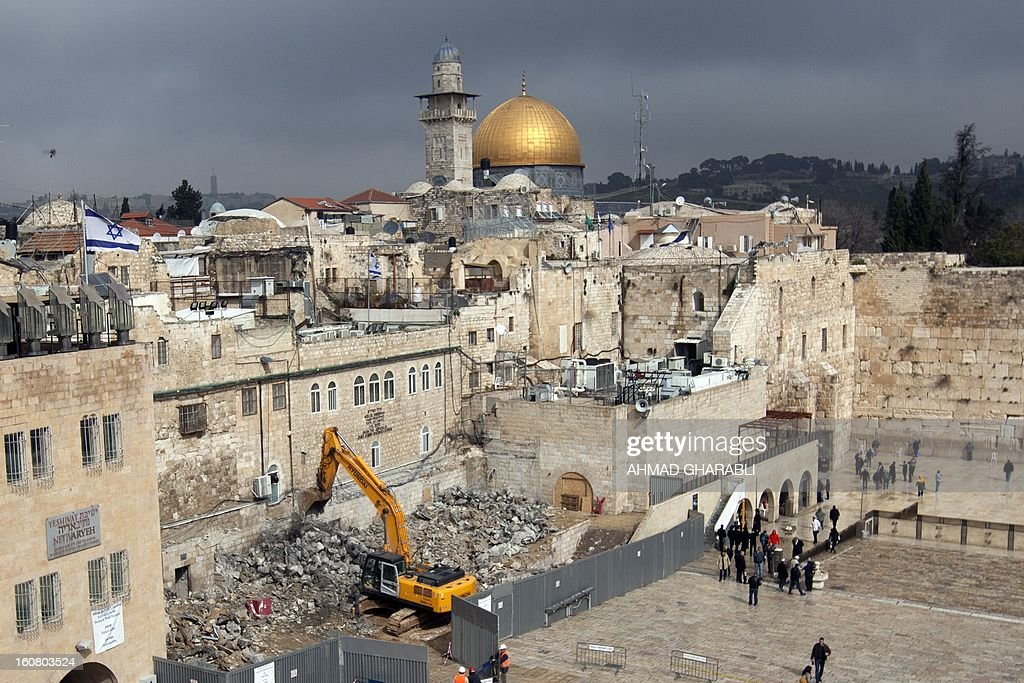 Labourers use a bulldozer to raze a Israeli building in the Western Wall plaza of Jerusalem's Old City with the Dome of the Rock mosque and Al Aqsa mosque compound in the background, on February 6, 2013. According to Al-Aqsa Foundation which campaigns for the defence of Islamic holy sites, the Israeli bulldozers are demolishing the frontages and arches of an historic Islamic building few dozen meters away from the Al-Aqsa mosque compound. The Al-Aqsa foundation said in a statement the demolition paves the way for an Israeli project to build a complex including a synagogue, a reception hall and a police station. AFP PHOTO/AHMAD GHARABLI