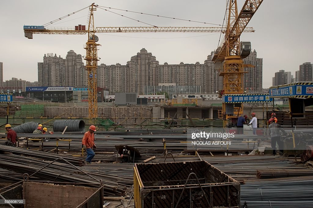 Labourers work at a construction site in Beijing on May 31, 2016. China's economy grew 6.7 percent in the three months of 2016, its slowest quarterly expansion in seven years, the government said, but indicators for March improved. / AFP / NICOLAS