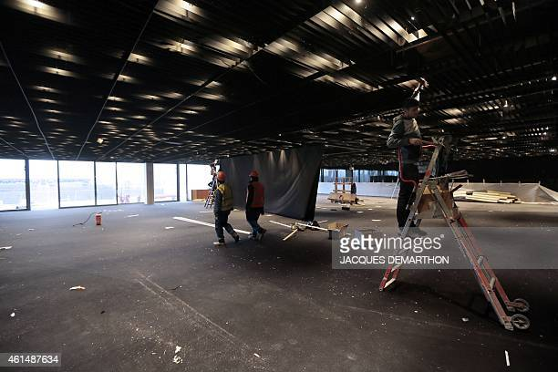 Labourers work at the grand reception hall of the new Philharmonie de Paris ahead of its opening in Paris on January 13 2015 The Philharmonie de...