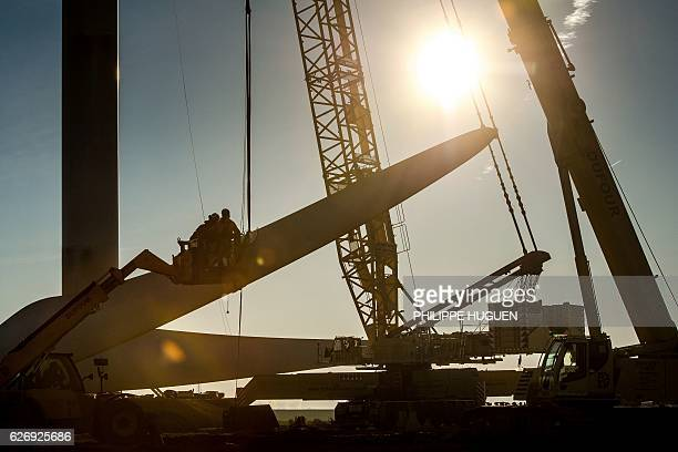 Labourers work at the installation site of a wind turbine in Leury northern France on November 30 2016 / AFP / PHILIPPE HUGUEN