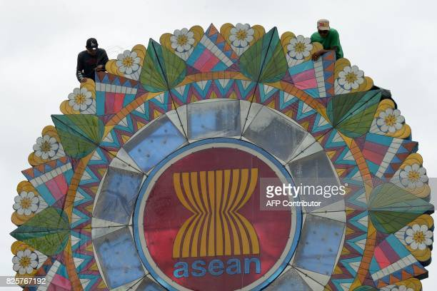 Labourers work on a giant lantern decorated with the logo for the Association of Southeast Asian Nations displayed at the entrance to the venue of...