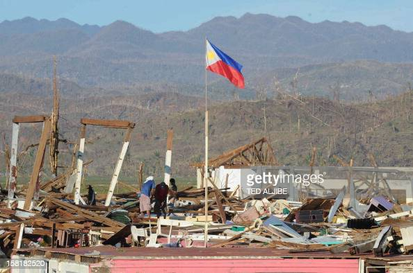 Labourers work on the damaged roof of a school building destroyed at the height of Typhoon Bopha in Cateel town Davao Oriental on December 11 2012...