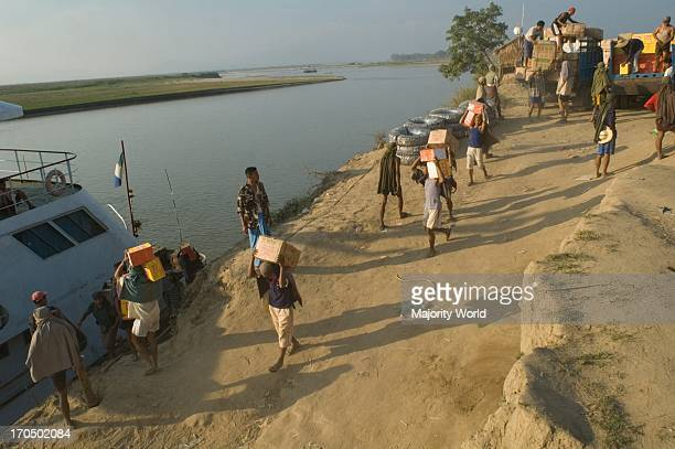 Labourers working at Bhamo jetty about three miles off town loading Chinamade goods onto a ferry bound for Mandalay
