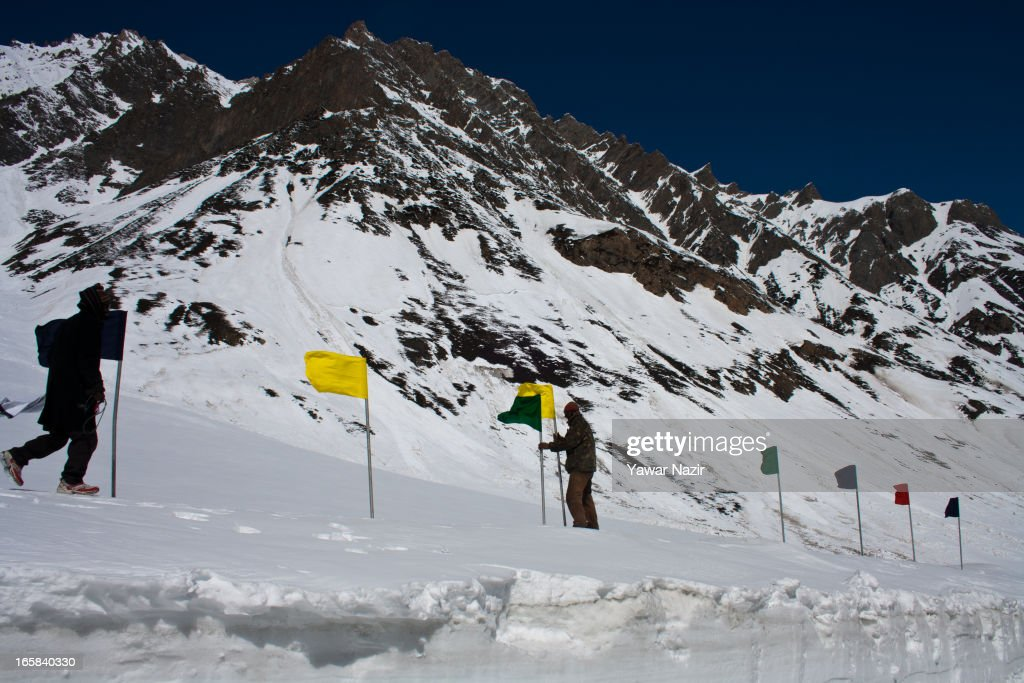 Labours erect flags in snow on Srinagar-Leh highway before reopening Srinagar-Leh highway on April 06, 2013 in Zojila, 108 km (67 miles) east of Srinagar, the summer capital of Indian administered Kashmir, India. The 443 km (275 miles) long Srinagar-Leh highway was opened for vehicular traffic by Indian Border Roads Organisation after remaining snowbound at Zojila Pass for the past six months. The pass connects Kashmir with Ladakh region a famous tourist destination among foreign tourists for its monasteries, landscapes and mountains.