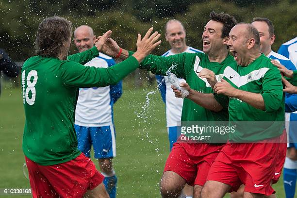 Labour's Shadow Home Secretary Andy Burnham celebrates with fellow parliamentarians and comedian John Bishop after winning a penalty shootout to...