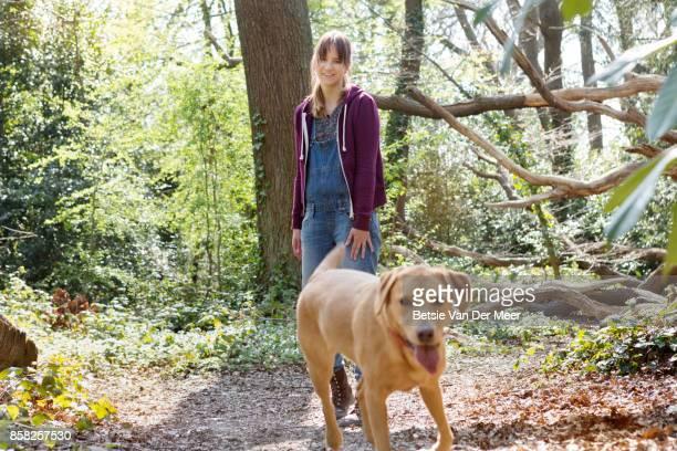 Labrador retriever runs towards camera, pet owner looks on smiling.