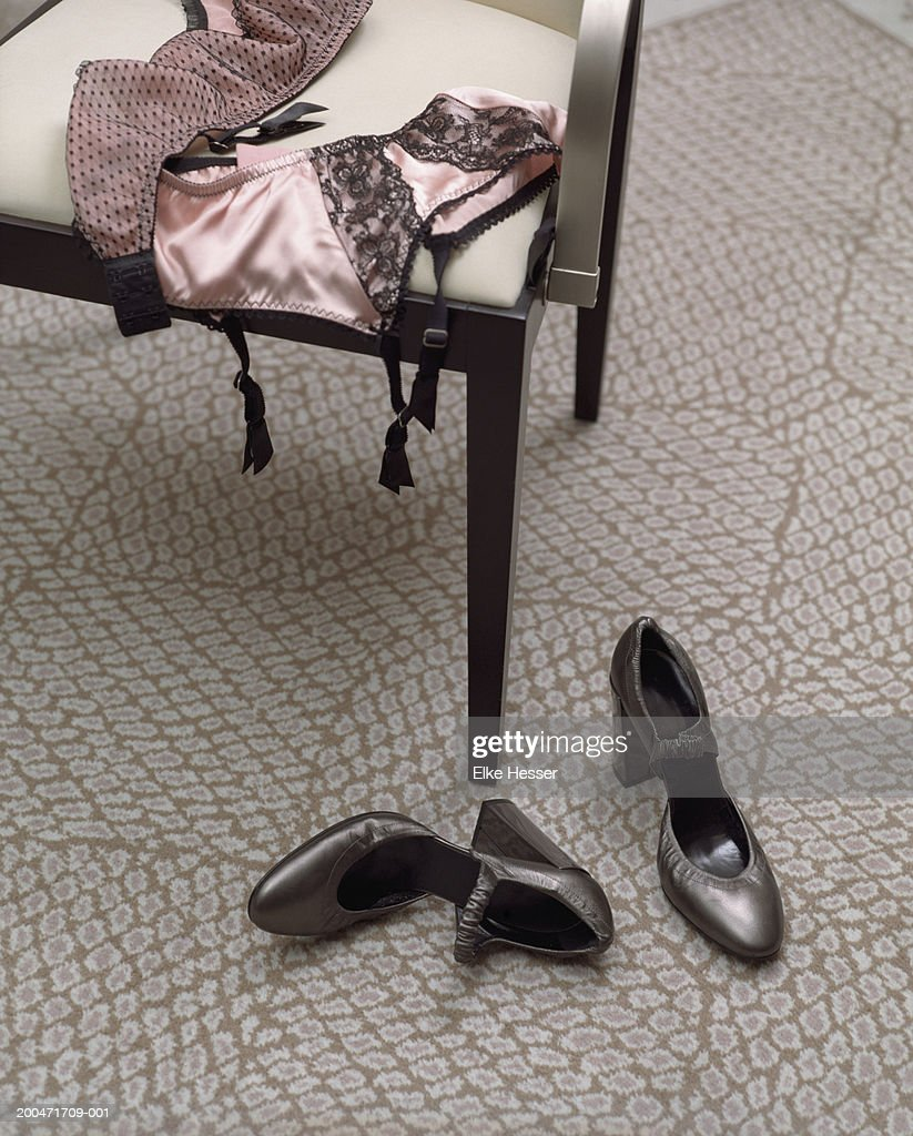 Lace underwear on chair by shoes on floor