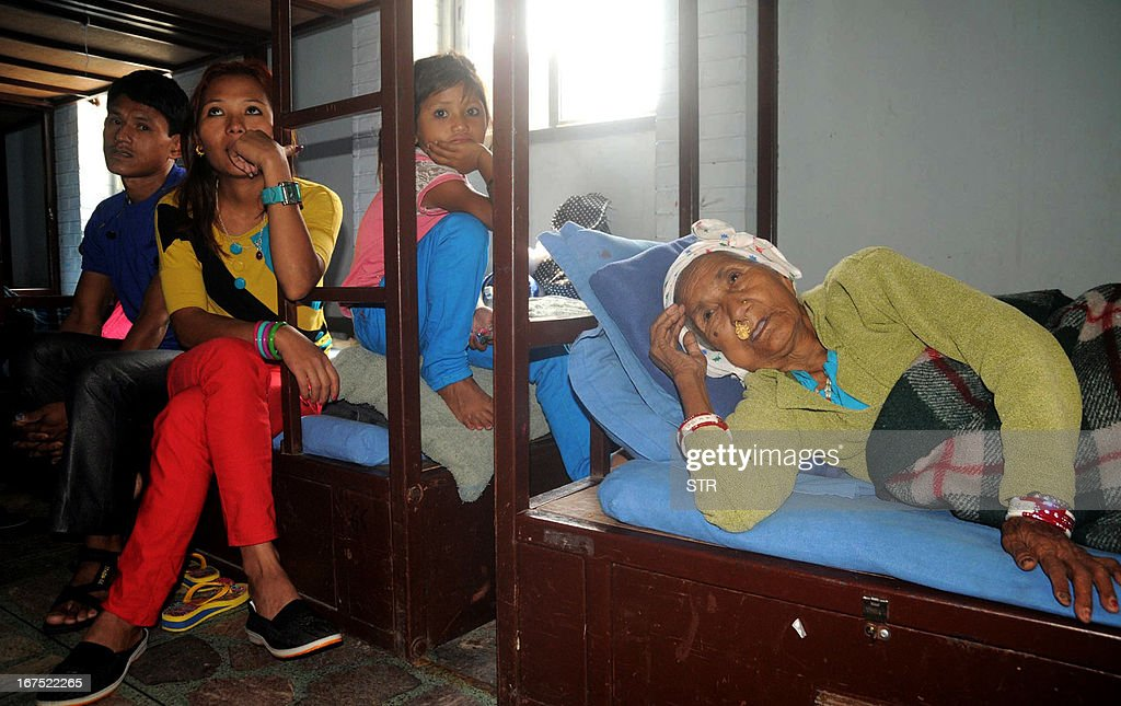 Lachhi Maya Ghising (R), 88, a Bhutanese refugee lies down near family members at a transit centre in Kathmandu on April 26, 2013, ahead of their flight to US under a United Nation resettlement programme. The refugees have been offered new lives in the United States and other nations following the failure of years of negotiations to secure their return to Bhutan, which says they were illegal immigrants. The United Nations refugee agency, UNHCR, said in a press statement on Friday that 100,000 have submitted applications for the resettlement so far. AFP PHOTO/ Keshab Thokar