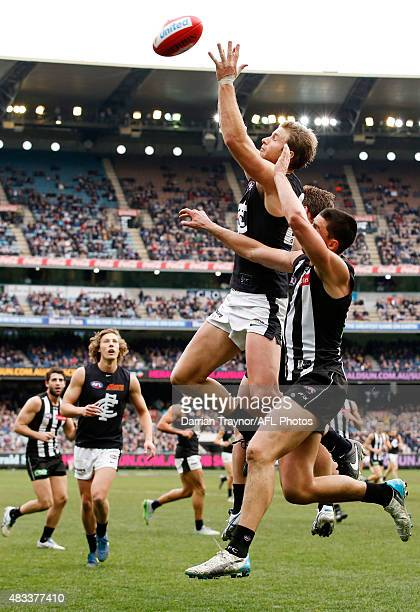 Lachie Henderson of the Blues attempts to mark as Scott Pendlebury of the Magpies applies pressure during the round 19 AFL match between the...