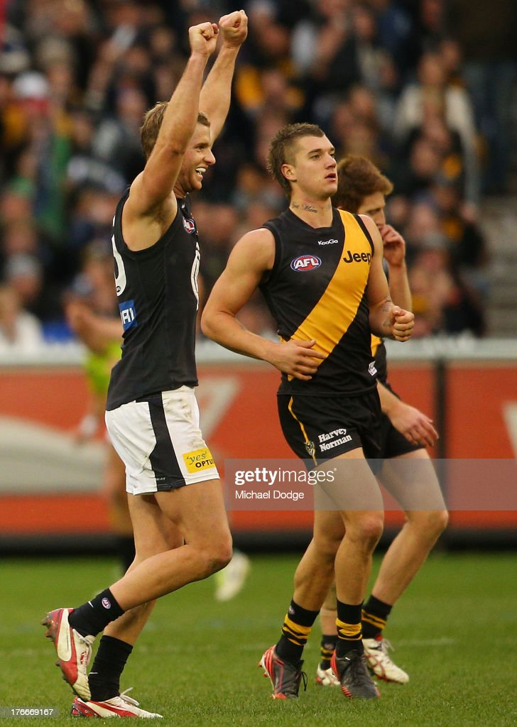 Lachie Henderson of the Blues celebrates the win on the final siren next to Dustin Martin of the Tigers during the round 21 AFL match between the Richmond Tigers and the Carlton Blues at Melbourne Cricket Ground on August 17, 2013 in Melbourne, Australia.