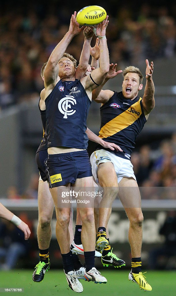 A Lachie Henderson (L) of the Blues marks the ball against Luke McGuane of the Tigers during the round one AFL match between the Carlton Blues and the Richmond Tigers at Melbourne Cricket Ground on March 28, 2013 in Melbourne, Australia.