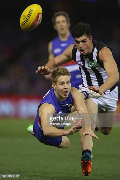 Lachie Hunter of the Bulldogs handballs away from Brayden Maynard of the Magpies during the round 17 AFL match between the Western Bulldogs and the...