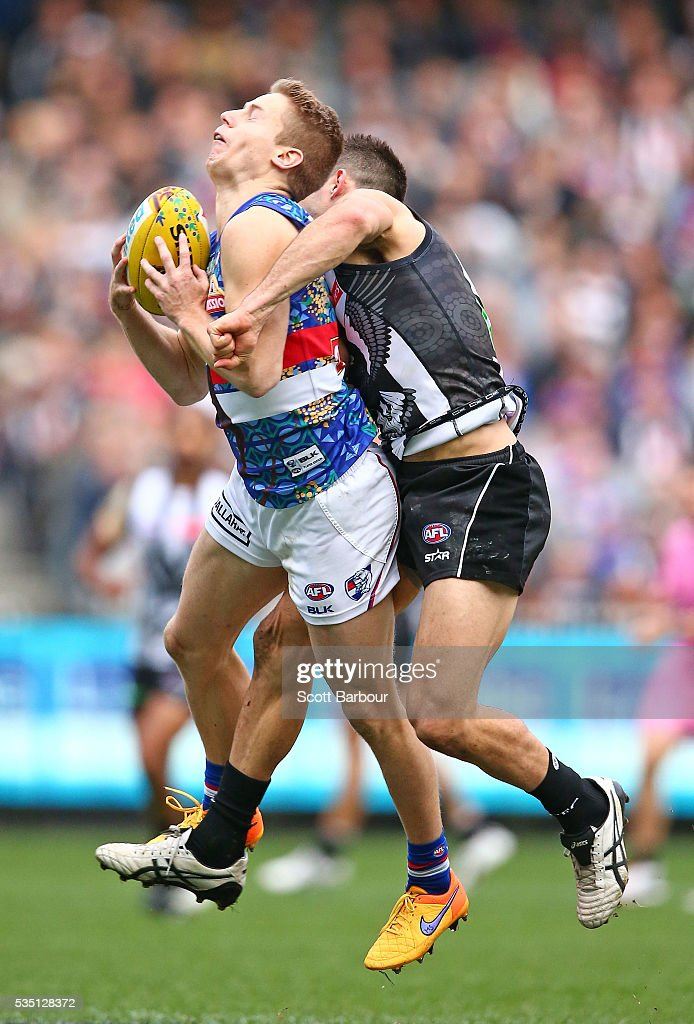 Lachie Hunter of the Bulldogs is tackled by Levi Greenwood of the Magpies during the round 10 AFL match between the Collingwood Magpies and the Western Bulldogs at Melbourne Cricket Ground on May 29, 2016 in Melbourne, Australia.