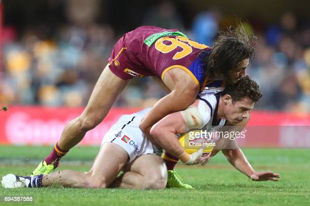 Lachie Neale is tackled by Rhys Mathieson of the Lions during the round 12 AFL match between the Brisbane Lions and the Fremantle Dockers at The...