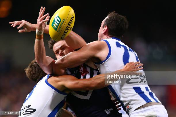 Lachie Neale of the Dockers gets tackled by Nathan Hrovat and Todd Goldstein of the Kangaroos during the round five AFL match between the Fremantle...