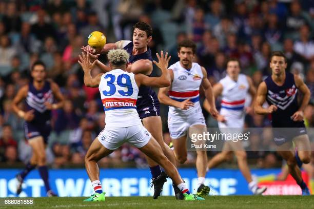 Lachie Neale of the Dockers handballs against Jason Johannisen of the Bulldogs during the round three AFL match between the Fremantle Dockers and the...