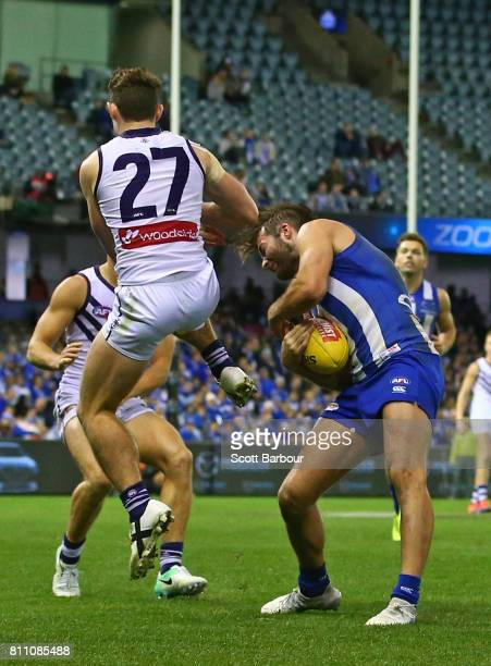 Lachie Neale of the Dockers hits Luke McDonald of the Kangaroos late and high inthe last quarter during the round 16 AFL match between the North...