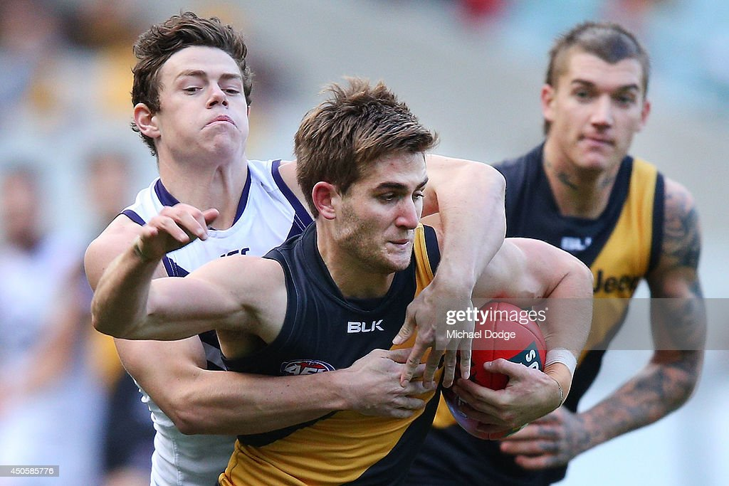 Lachie Neale of the Dockers tackles Anthony Miles of the Tigers during the round 13 AFL match between the Richmond Tigers and the Fremantle Dockers at Melbourne Cricket Ground on June 14, 2014 in Melbourne, Australia.