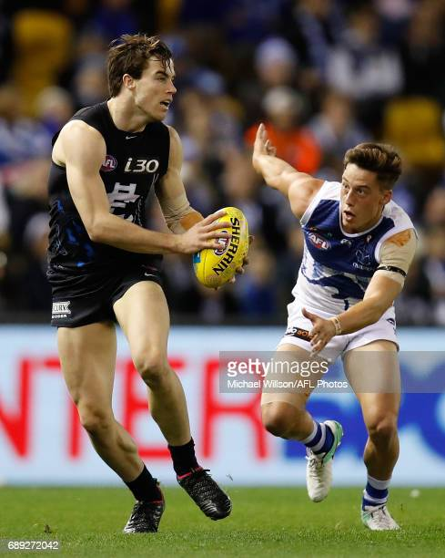 Lachie Plowman of the Blues is chased by Nathan Hrovat of the Kangaroos during the 2017 AFL round 10 match between the Carlton Blues and the North...