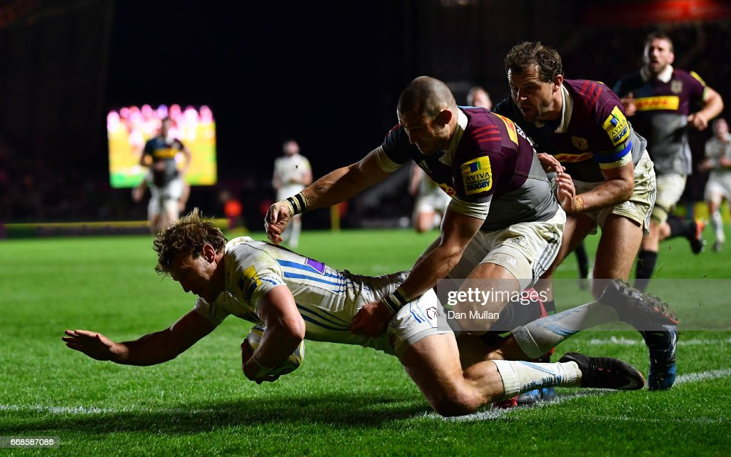 Lachie Turner of Exeter Chiefs dives over for a try under pressure from Mike Brown and Nick Evans of Harlequins during the Aviva Premiership match between Harlequins and Exeter Chiefs at Twickenham Stoop on April 14, 2017 in London, England.