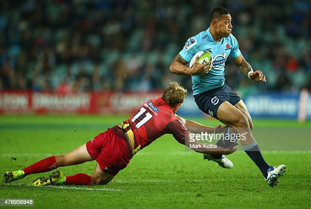 Lachie Turner of the Reds is evaded by Israel Folau of the Waratahs during the round 18 Super Rugby match between the Waratahs and the Reds at...