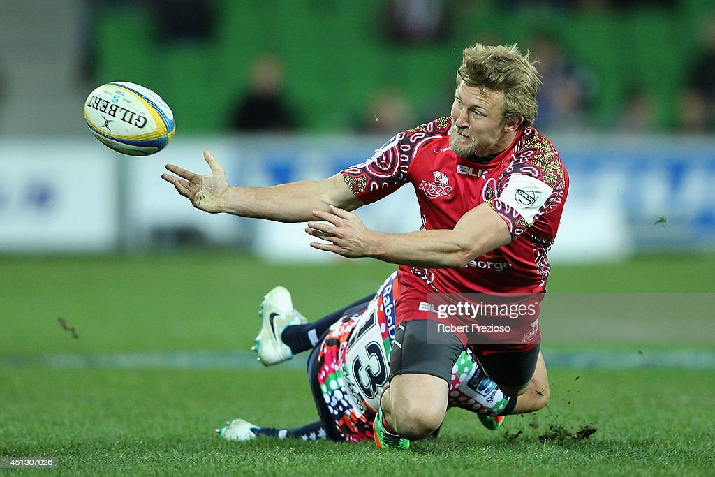 Lachie Turner of the Reds offloads the ball as Tamati Ellison of the Rebels applies a tackle during the round 17 Super Rugby match between the Rebels and the Reds at AAMI Park on June 27, 2014 in Melbourne, Australia.
