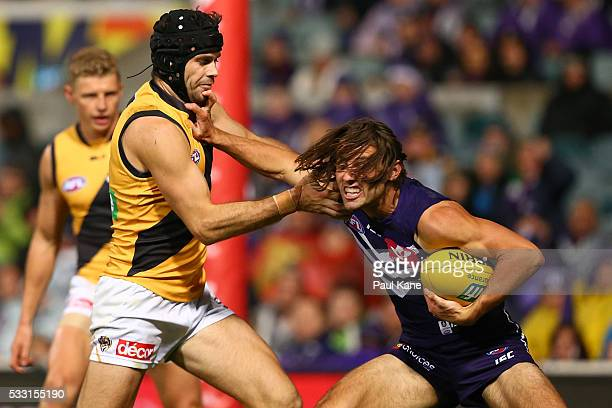 Lachie Weller of the Dockers fends off a tackle by Trent Cotchin of the Tigers during the round nine AFL match between the Fremantle Dockers and the...