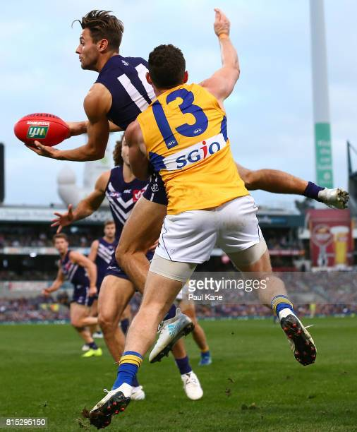 Lachie Weller of the Dockers handballs against Luke Shuey of the Eagles during the round 17 AFL match between the Fremantle Dockers and the West...