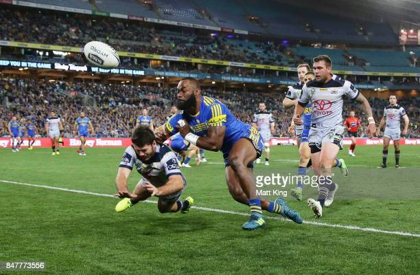 Lachlan Coote of the Cowboys punches the ball awat from Semi Radradra of the Eels during the NRL Semi Final match between the Parramatta Eels and the...