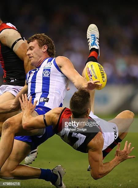 Lachlan Hansen of the Kangaroos crashes into Patrick Ambrose of the Bombers who marks the ball during the round one AFL match between the North...