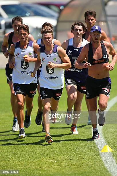 Lachlan Weller Ed Langdon and Connor Blakely run laps with Luke McPharlin Alex Silvagni and Paul Duffield of the Dockers during a Fremantle Dockers...