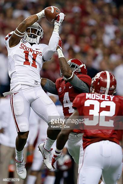 Lacoltan Bester of the Oklahoma Sooners catches a pass over TJ Yeldon of the Alabama Crimson Tide during the Allstate Sugar Bowl at the MercedesBenz...