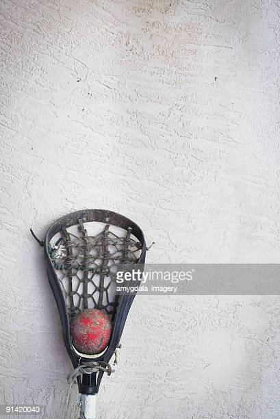 lacrosse stick head and red ball leaning against wall