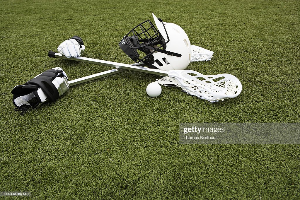 Lacrosse sticks, gloves, balls and sports helmet on artificial turf : Stock Photo