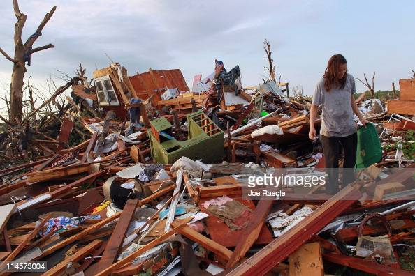 Lacy Tasker salvages what she can from her mothers house after it was destroyed when a massive tornado passed through the town on May 24 2011 in...